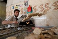 A baker takes out bread baked in a wood-fired oven due to fuel shorages in Sanaa