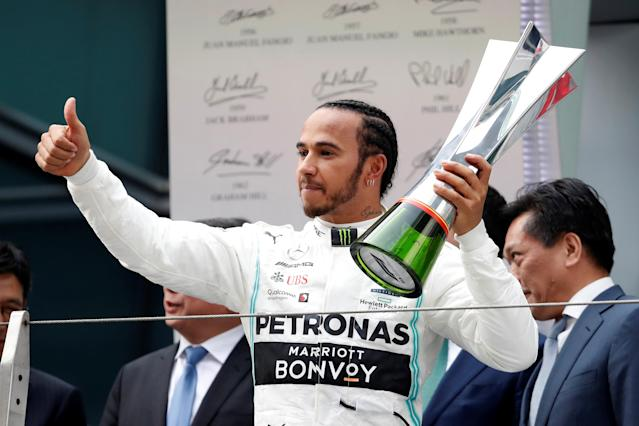 Mercedes' Lewis Hamilton celebrates winning the race on the podium with the trophy (Photo: REUTERS/Aly Song)