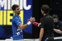 Novak Djokovic of Serbia, left, shakes hands with Dominic Thiem of Austria at the of their semifinal match ATP World Finals tennis tournament at the O2 arena in London, Saturday, Nov. 21, 2020. Thiem beat the top-ranked Djokovic 7-5, 6-7 (10), 7-6 (5). (AP Photo/Frank Augstein)