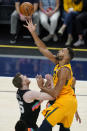 Utah Jazz center Rudy Gobert, right, shoots as San Antonio Spurs center Jakob Poeltl, left, defends in the first half during an NBA basketball game Monday, May 3, 2021, in Salt Lake City. (AP Photo/Rick Bowmer)