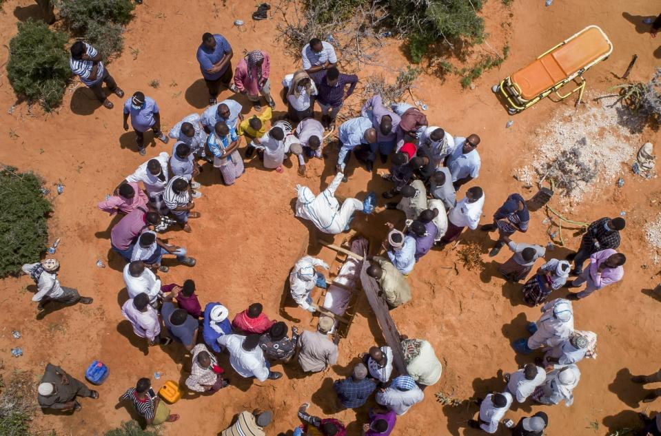 FILE - In this April 30, 2020, file photo, medical workers in protective suits bury the body of an elderly man believed to have died from the coronavirus in Mogadishu, Somalia. A new snapshot of the frantic global response to the coronavirus pandemic shows some of the world's largest government donors of humanitarian assistance are buckling under the strain and overall aid commitments have dropped by a third from the same period last year. (AP Photo, File)