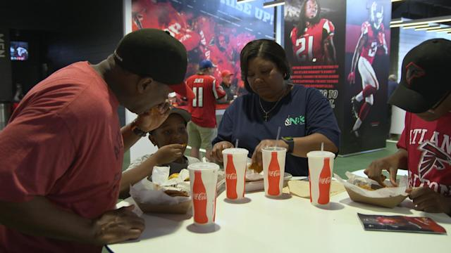 A family eats before an Atlanta Falcons preseason game on Aug. 31, 2017. (Catherine Newman/Oath)