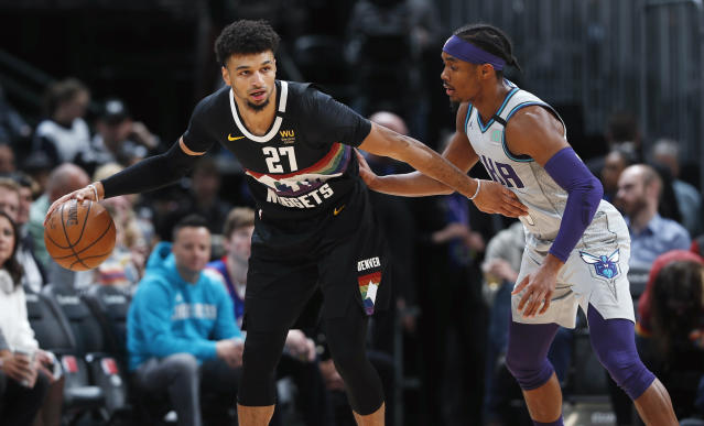 Denver Nuggets guard Jamal Murray, left, keeps Charlotte Hornets guard Devonte' Graham at bay during the first half of an NBA basketball game Wednesday, Jan. 15, 2020, in Denver. (AP Photo/David Zalubowski)