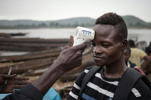 A health worker in the Central African Republic monitors the temperature of a young traveller from DRCongo