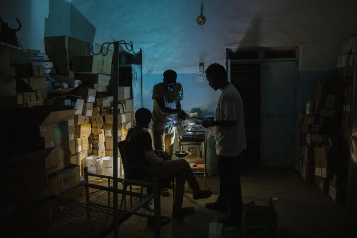 """Surgeon and doctor-turned-refugee, Dr. Tewodros Tefera, checks a Tigrayan refugee inside the Sudanese Red Crescent clinic, at Hamdayet Transition Center near the Sudan-Ethiopia border, eastern Sudan, on March 23, 2021. Tewodros fills a growing number of notebooks as he compiles a """"dossier"""" on the Tigray conflict. Sometimes he dreams of taking it to the International Criminal Court in a quest for justice. (AP Photo/Nariman El-Mofty)"""