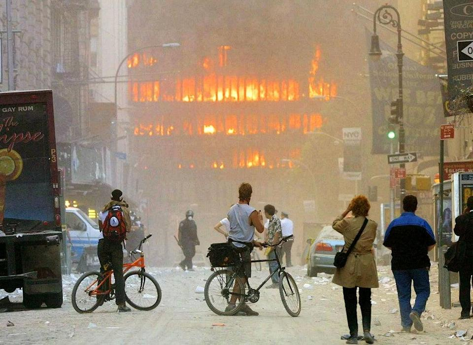 People look down the street at the World Trade Center in flames (Getty)