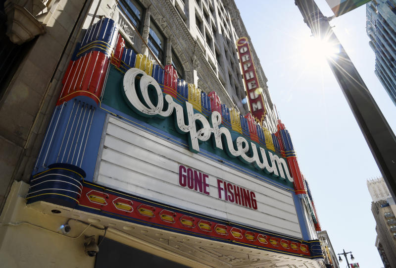 """FILE - In this March 25, 2020 file photo, a """"Gone Fishing"""" message is posted on the closed Orpheum Theatre's marquee in Los Angeles. Movie theaters may be closed, but friends are still finding ways to watch together while staying apart thanks to applications like Netflix Party. Movie studios are getting in on the action too, with """"watch parties"""" for old favorites like """"Legally Blonde"""" and new releases like """"Emma"""" on Facebook and Twitter. (AP Photo/Chris Pizzello, File)"""