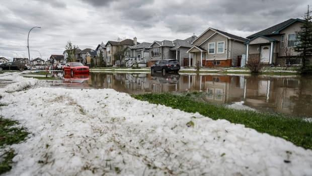 Residents began cleaning up in Calgary on June 14, 2020, after a major hailstorm caused widespread damage and flooding. (Jeff McIntosh/The Canadian Press - image credit)