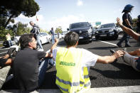 Alitalia workers block the highway leading to the Rome Leonardo Da Vinci international airport, as they stage a protest in Fiumicino, Friday, Sept. 24, 2021. Alitalia, which has been in the red for more than a decade, is due to formally exit the airline market next month and be replaced by a new national carrier ITA, or Italy Air Transport. The European Commission has given the go-ahead to a 1.35 billion euro ($1.58 billion) injection of government funding into the new airline, but ITA is only planning to hire around a quarter of the estimated 10,000 Alitalia employees.(Cecilia Fabiano/LaPresse via AP)