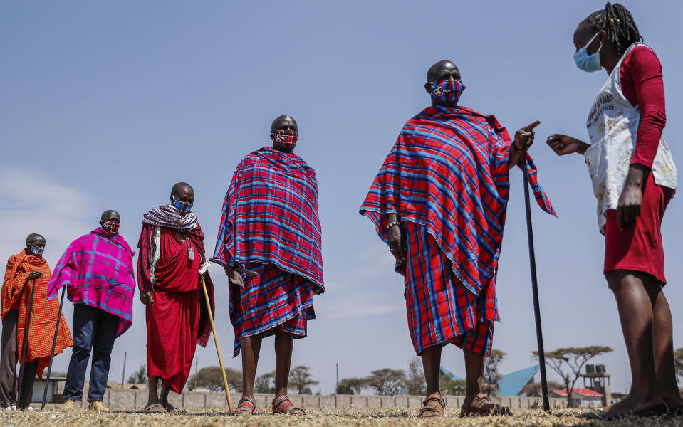 Maasai men queue to receive the AstraZeneca coronavirus vaccine at a clinic in Kimana, southern Kenya Saturday, Aug. 28, 2021. Wealthier nations are awash in vaccines, while they are scarce in poorer countries and many people are still waiting for their first shot. (AP Photo/Brian Inganga)