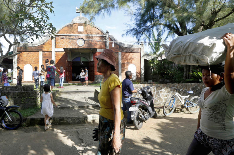 In this Jan. 27, 2019 photo, pedestrians walk past the chapel built by U.S. priest Father Pius Hendricks in the village of Talustusan on Biliran Island in the central Philippines. Since December 2018, the small village has been rocked by controversy after about 20 boys and men accused the Catholic parish priest of years of alleged sexual abuse. (AP Photo/Bullit Marquez)