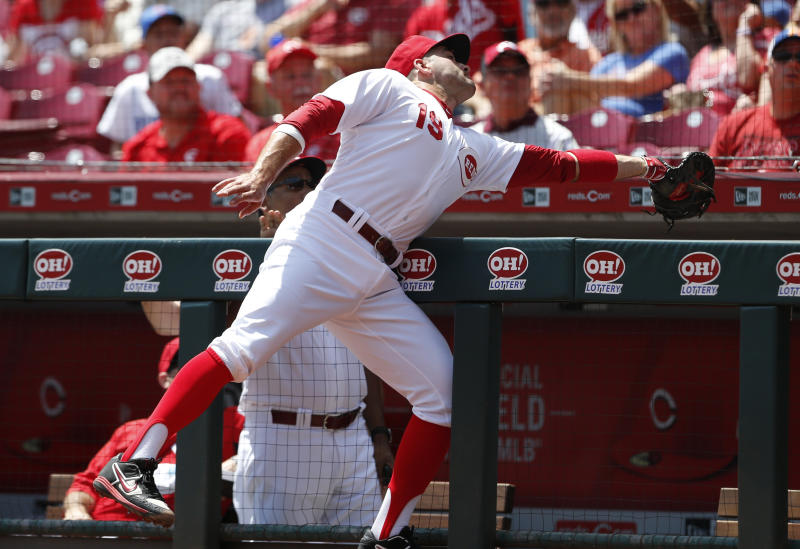Cincinnati Reds first baseman Joey Votto leans into the dugout to catch a foul ball off the bat of Chicago Cubs' Anthony Rizzo during the first inning of a baseball game, Sunday, Aug. 11, 2019, in Cincinnati. (AP Photo/Gary Landers)
