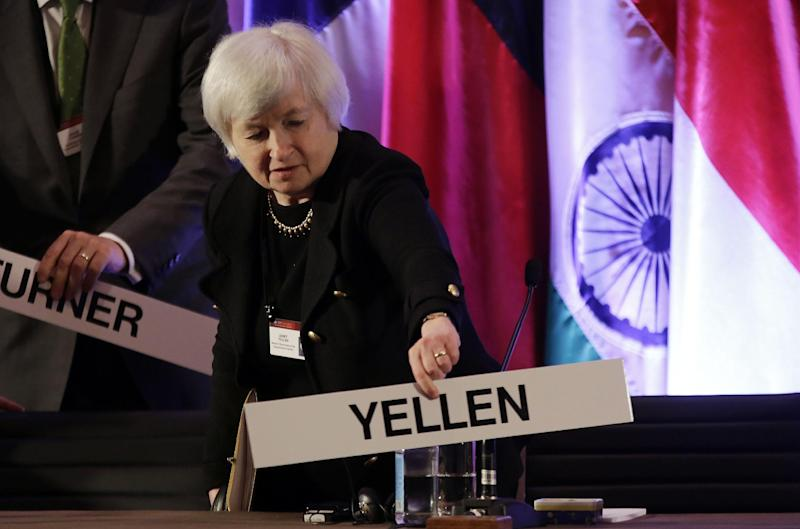 FILE - In this  Monday, June 3, 2013, file photo, Janet Yellen, vice chair of the Board of Governors of the Federal Reserve System, places her name plate at her seat at the International Monetary Conference in Shanghai, China. As of Sunday, Sept. 15, 2013, Yellen is the clear front-runner to be nominated as chair of the federal Reserve. (AP Photo/Eugene Hoshiko, File)