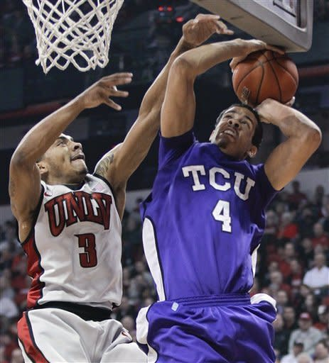 TCU's Amric Fields (4) hits the bottom of the backboard while attempting a shot against UNLV's Anthony Marshall (3)in the first half of an NCAA college basketball game, Wednesday, Jan. 18, 2012, in Las Vegas. (AP Photo/Julie Jacobson)