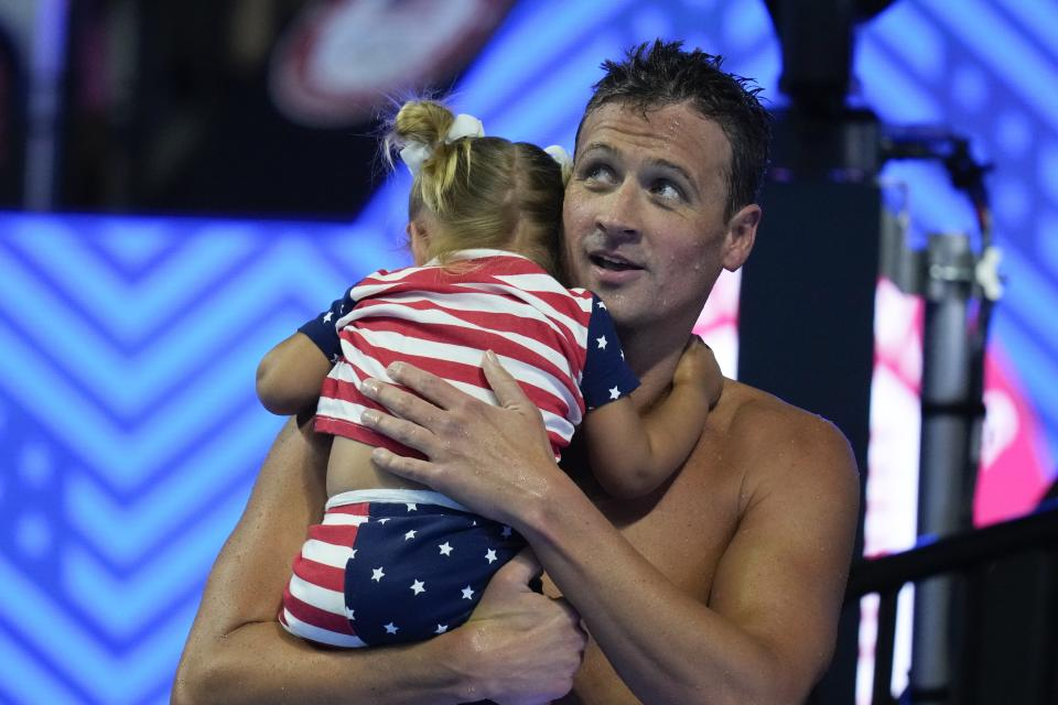 Ryan Lochte holds his daughter after his heat in the men's 200 Individual Medley during wave 2 of the U.S. Olympic Swim Trials on Thursday, June 17, 2021, in Omaha, Neb. (AP Photo/Charlie Neibergall)