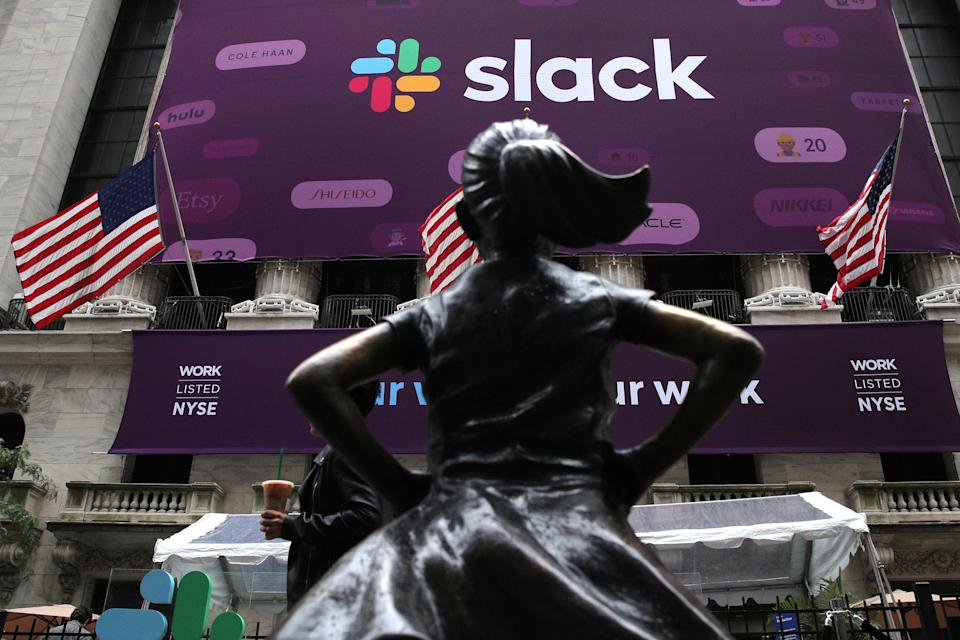 """The Slack Technologies Inc. logo is seen behind the """"Fearless Girl"""" statue outside the New York Stock Exchange (NYSE) during the company's IPO in New York, U.S. June 20, 2019.  REUTERS/Brendan McDermid"""