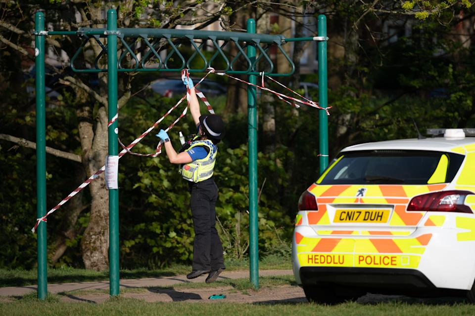 CARDIFF, UNITED KINGDOM - APRIL 11: A police officer jumps to puts tape on exercise equipment at Roath recreation ground after a man was seen using the equipment on April 11, 2020 in Cardiff, United Kingdom. Police have stepped up patrols to prevent people from travelling to beaches and beauty spots over the Easter weekend. The Coronavirus (COVID-19) pandemic has spread to many countries across the world, claiming over 100,000 lives and infecting over 1 million people. (Photo by Matthew Horwood/Getty Images)