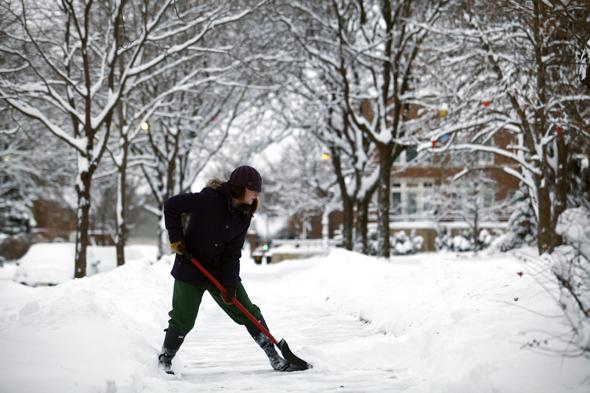 DETROIT, MI - JANUARY 6: Carly Strachan shovels several inches of snow from her sidewalk as the area deals with record breaking freezing weather January 6, 2014 in Detroit, Michigan. Michigan and most of the Midwest received their first major snow storm of 2014 last week and subzero temperatures are expected most of this week with wind-chill driving temperatures down to 50-70 degrees below zero. A