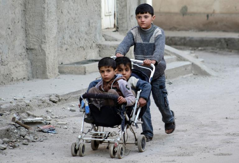 A boy carries two younger boys in a pushchair on February 8, 2014 in a street of the northeastern Syrian city of Deir Ezzor