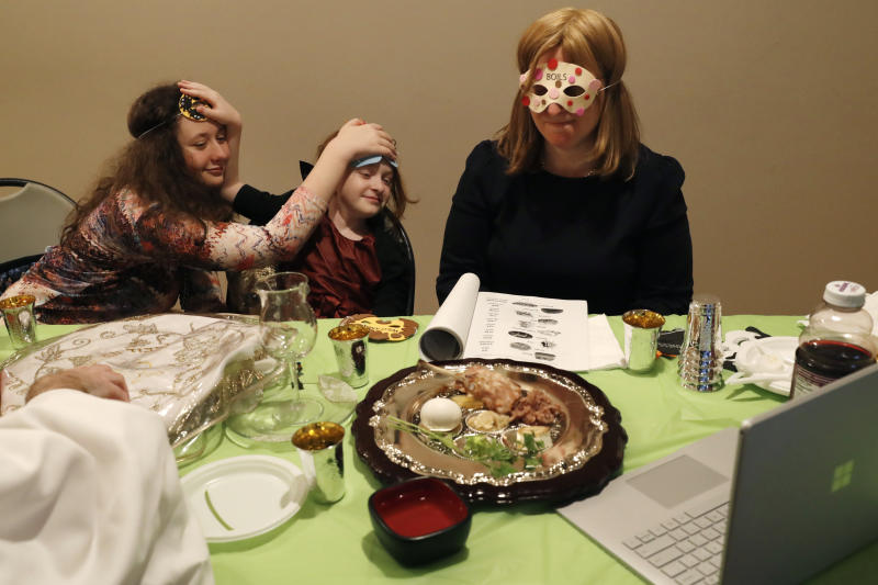 "Wearing masks depicting some ten plagues inflicted on Egyptians during ancient times, Shira Segal, left, and younger sister Rayna, 8, center, clown around in front of a laptop computer broadcasting their Passover seder, as their mother Adina, right, dons a mask representing ""boils,"" during the servie for members of their congregation, friends and family, from their home in the Sheepshead Bay section of Brooklyn during the current coronavirus outbreak, Wednesday, April 8, 2020, in New York. With the deadly COVID-19 virus in full swing in New York and around the country, the reading of the plagues is particularly resonant this year. According to the story, after Pharaoh refused Moses' pleas to let enslaved Israelites go free, God sent a series of ten plagues to pressure the Egyptian ruler. Each time Pharaoh promises to free the Israelites, but reverses his decision when the plague is lifted, until the last one. The plagues are: water turning to blood, frogs, lice, flies, livestock pestilence, boils, hail, locusts, darkness and the killing of first-born children. Passover commemorates the Israelites' freedom from slavery in ancient Egypt in the wake of the ten plagues. (AP Photo/Kathy Willens)"