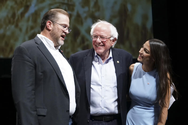 Kansas congressional candidate James Thompson, left, U.S Sen. Bernie Sanders, I-Vt., and Alexandria Ocasio-Cortez, a Democratic congressional candidate from New York, stand together on stage after a rally, Friday, July 20, 2018, in Wichita, Kan. (Jaime Green/The Wichita Eagle via AP)