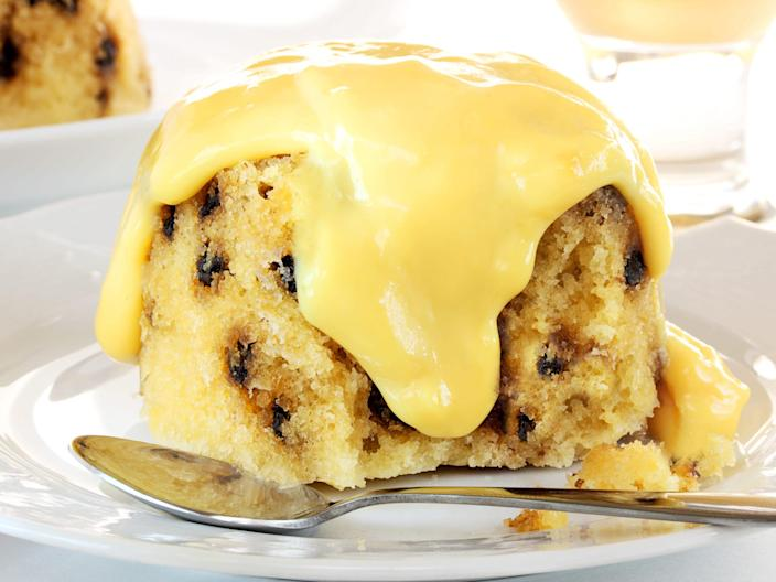spotted dick pudding with custard on top of a plate and spoon