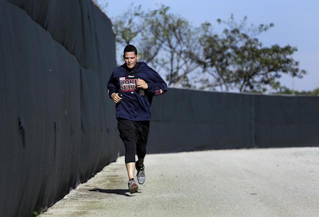 St. Louis Cardinals catcher Yadier Molina jogs along a warning track during an informal spring training baseball practice Wednesday, Feb. 12, 2014, in Jupiter, Fla. Cardinals pitchers and catchers first official practice is scheduled for Thursday. (AP Photo/Jeff Roberson)