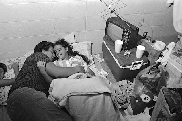 FILE - In this Friday, Aug. 30, 1985, file photo taken by Dave Martin, Mark Bailey holds his fiance Belinda Mammack as they relax in an emergency shelter at Theodore High School, Ala. Martin, a longtime Associated Press photographer based in Montgomery, Ala., died after collapsing on the Georgia Dome field at the Chick-fil-A Bowl on Tuesday, Dec. 31, 2013. Martin was 59. (AP Photo/Dave Martin, File)