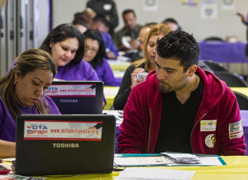 SEIU-UHW worker Kathy Santana, left , assists Ruben Torres, 27, during a health care enrollment event at SEIU-UHW office, Monday, March 31, 2014, in Commerce, Calif. Monday is the deadline to sign up for private health insurance in the new online markets created by President Barack Obama's health care law. (AP Photo/Ringo H.W. Chiu)