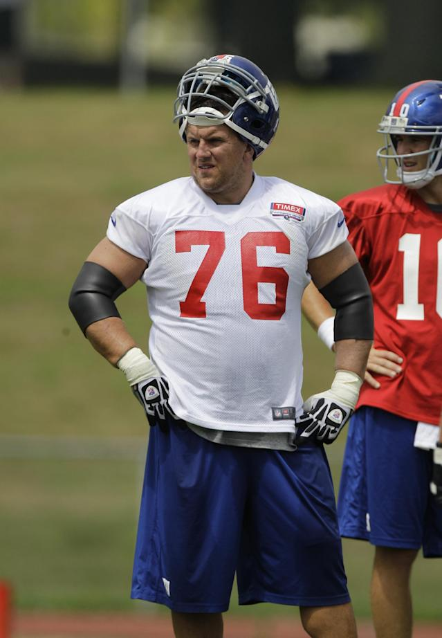 FILE - In this July 27, 2012 file photo, New York Giants guard Chris Snee (76) and Eli Manning wait out a break in practice at the New York Giants NFL football training camp in Albany, N.Y. Snee, the 32-year-old son-in-law of coach Tom Coughlin, is retiring from the Giants because of a series of injuries. Snee met with the team Monday, July 21, 2014, then decided to end his NFL career after 10 seasons. (AP Photo/Kathy Willens, File)