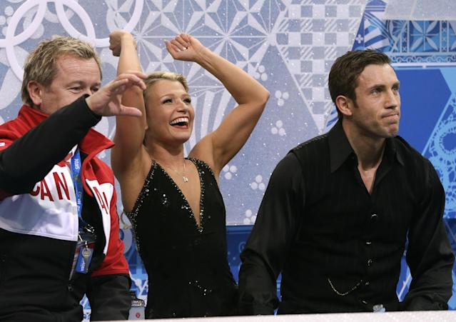 Kirsten Moore-Towers, centre, gestures as she and Dylan Moscovitch of Canada wait in the results area after competing in the pairs free skate figure skating competition at the Iceberg Skating Palace during the 2014 Winter Olympics, Wednesday, Feb. 12, 2014, in Sochi, Russia. (AP Photo/Darron Cummings)