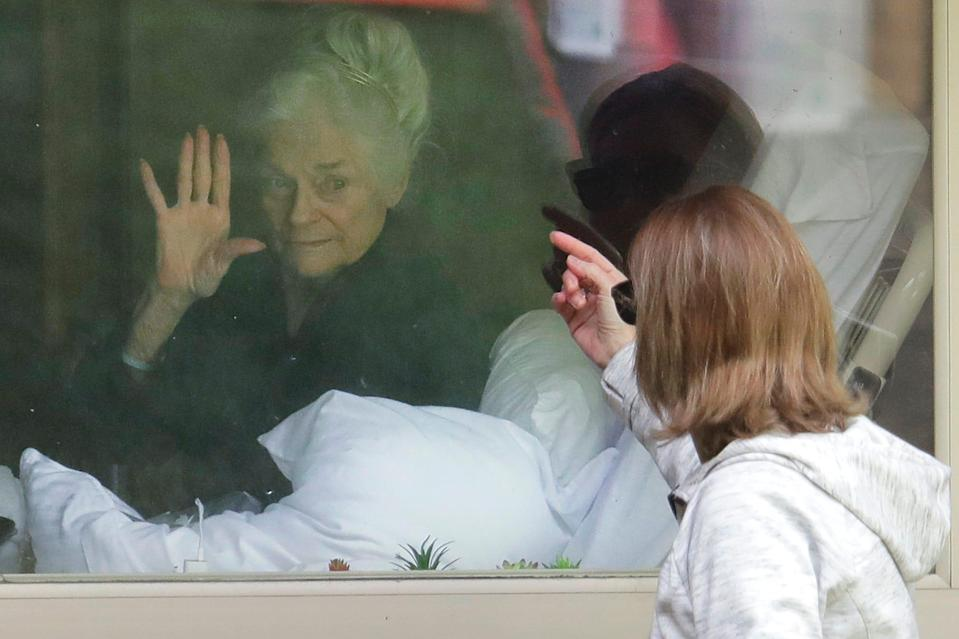 Judie Shape, left, who has tested positive for the coronavirus, waves to her daughter, Lori Spencer, on March 11, 2020, as they visit on the phone and look at each other through a window at the Life Care Center.