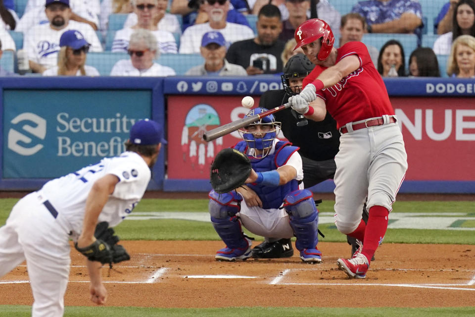 Philadelphia Phillies' Rhys Hoskins, right, hits a solo home run as Los Angeles Dodgers starting pitcher Clayton Kershaw, left, watches along with catcher Austin Barnes, second from left, and home plate umpire Manny Gonzalez during the first inning of a baseball game Wednesday, June 16, 2021, in Los Angeles. (AP Photo/Mark J. Terrill)