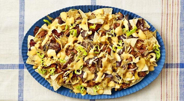 """<p>This nacho mash-up is the ultimate game day snack. Shaved steak, melted cheese, and a pop of pepperoncini bring cheesesteak flavors to everyone's favorite app. </p><p><a href=""""https://www.thepioneerwoman.com/food-cooking/recipes/a34224728/cheesesteak-nachos-with-chipotle-beans/"""" rel=""""nofollow noopener"""" target=""""_blank"""" data-ylk=""""slk:Get Ree's recipe."""" class=""""link rapid-noclick-resp""""><strong>Get Ree's recipe.</strong></a></p>"""