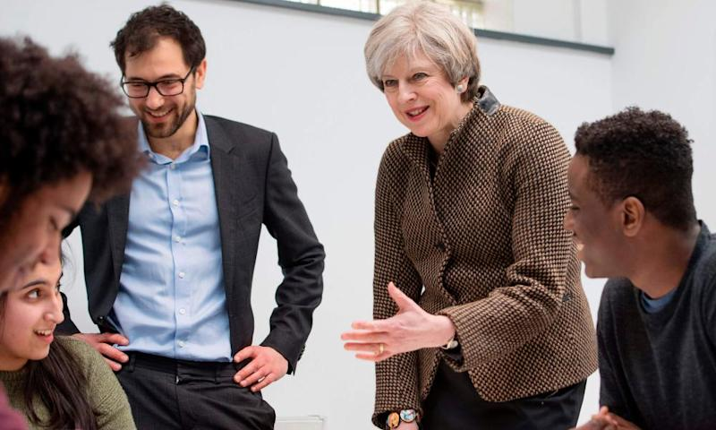 Theresa May speaks with headteacher Dan Abramson, left, and students at King's College London Mathematics school, a free school.