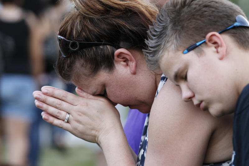"Dylan Bowen, 13, right, holds onto his mother Lorri Hastings, as they pray, Sunday, July 22, 2012 in Aurora, Colo., during a prayer vigil for the victims of Friday's mass shooting at a movie theater. Twelve people were killed and dozens were injured in a shooting attack early Friday at the packed theater during a showing of the Batman movie, ""The Dark Knight Rises."" Police have identified the suspected shooter as James Holmes, 24. (AP Photo/Alex Brandon)"