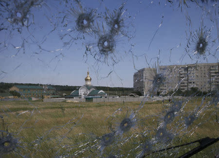 A Ukrainian border post is seen through bullet holes in a truck's windscreen on the outskirts of the eastern Ukrainian city of Luhansk