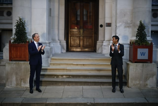 Foreign Secretary Dominic Raab, left, and Chancellor Rishi Sunak clapping outside the Foreign and Commonwealth Office in London to salute local heroes during Thursday's nationwide Clap for Carers initiative