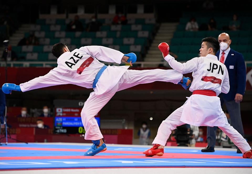 <p>Japan's Naoto Sago (R) competes against Azerbaijan's Firdovsi Farzaliyev in the men's kumite -67kg elimination round of the karate competition during the Tokyo 2020 Olympic Games at the Nippon Budokan in Tokyo on August 5, 2021. (Photo by Alexander NEMENOV / AFP)</p>