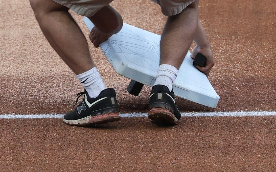 A grounds crewman installed third base before the Louisville Bats hosted the St. Paul Saints during their game at Slugger Field in Louisville, Ky. on June 2, 2021.