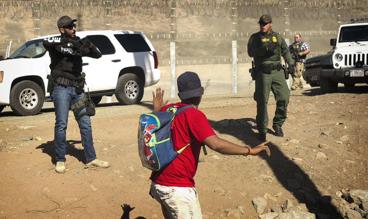 A Central American migrant is stopped by U.S. agents who order him to go back to the Mexican side of the border, after a group of migrants got past Mexican police at the Chaparral crossing in Tijuana, Mexico, Sunday, Nov. 25, 2018, at the border with San Ysidro, California. (Photo: Pedro Acosta/AP)