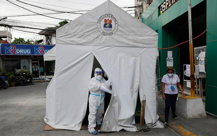 A health worker wearing a protective suit goes out of a tent with Covid-19 patients outside a hospital in Manila, Philippines - Aaron Favila/AP