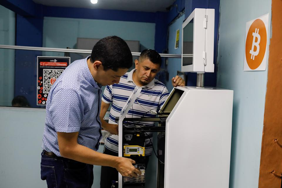 Edgar Borja and Edwin Escobar check the parts of a K1 ATM prototype, which is designed for handling cash, card payments, Bitcoin and receiving remittances, in Santa Tecla, El Salvador June 25, 2021. REUTERS/Jose Cabezas