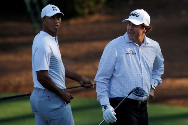 FILE PHOTO: U.S. golfers Woods and Mickelson walk to the 11th tee during practice for the 2018 Masters golf tournament in Augusta