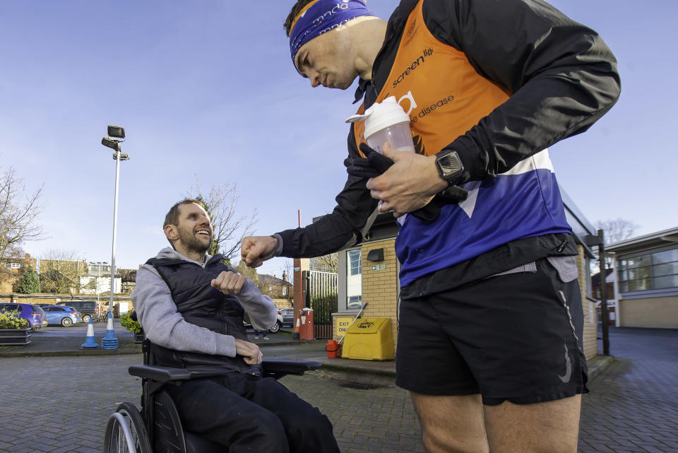 Sinfield is greeted by former team-mate Rob Burrow at Headingley after the fifth leg of his 7 in 7 challenge