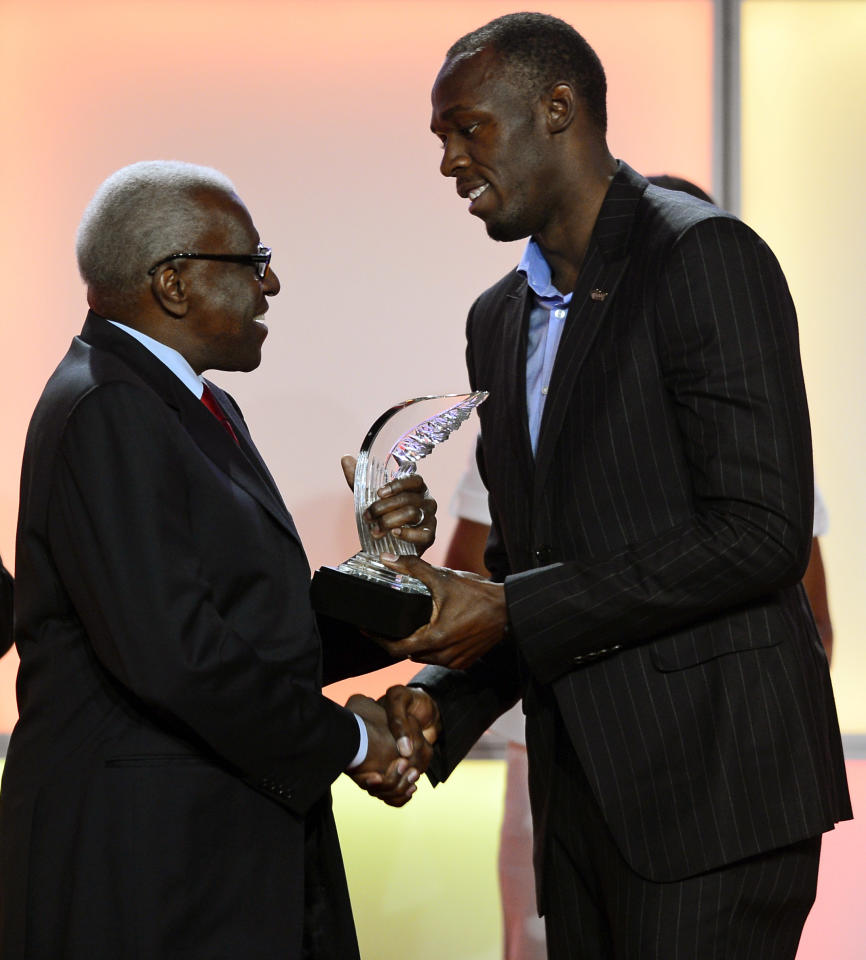 President of the IAAF Lamine Diack, left, presents the Athlete of the Year Award to Jamaican athlete Usain Bolt, during an event marking the centenary of the IAAF (International Association of Athletics Federations), in Barcelona, Spain, Saturday, Nov. 24, 2012. (AP Photo/Manu Fernandez)