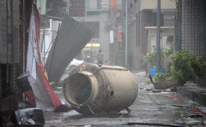 A man walks behind a tank that was blown down on the street as Typhoon Soudelor hits Taipei on August 8, 2015 (AFP Photo/Sam Yeh)