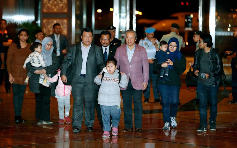 Malaysians walk with Foreign minister Anifah Aman, centre right, after arriving at Kuala Lumpur airport - AP