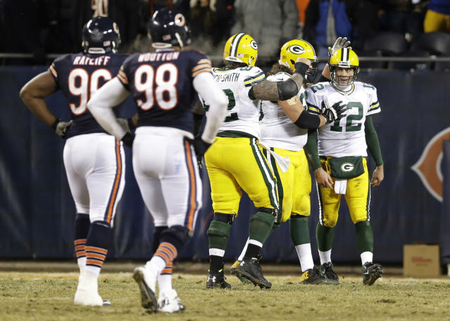 Green Bay Packers quarterback Aaron Rodgers (12) celebrates a game-winning touchdown pass with his teammates during the second half of an NFL football game against the Chicago Bears, Sunday, Dec. 29, 2013, in Chicago. The Packers won 33-28 to capture the NFC North title. (AP Photo/Nam Y. Huh)
