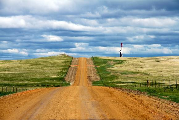 A drilling rig beside a long dirt road